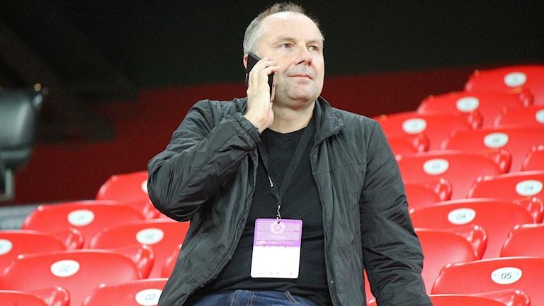 Man sitter på tom fotbollsläktare och pratar i mobiltelefon