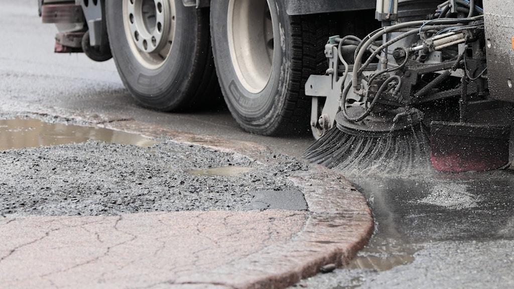 Hjul och sop på fordon som sopar bort grus från en gata