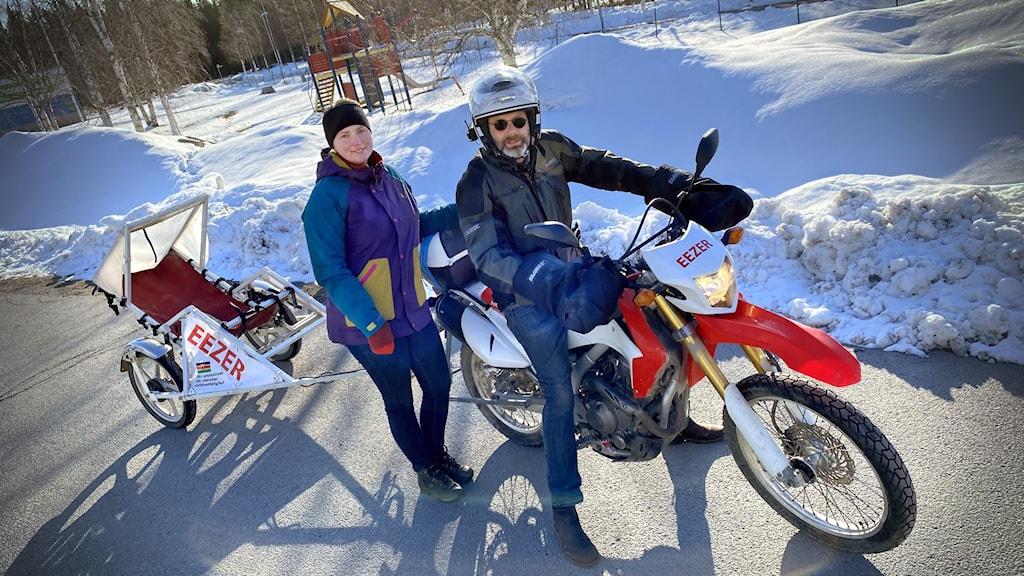 En man sitter på en cross-motorcykel, och en kvinna står bredvid. En vagn är kopplad till motorcykeln.