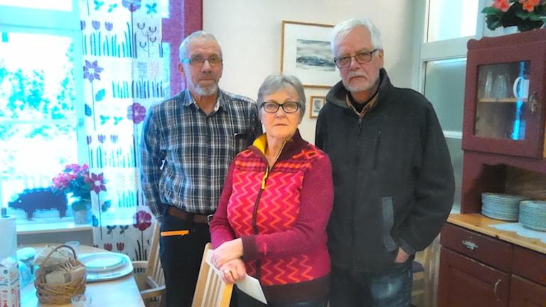 En kvinna och två män i ett kök.