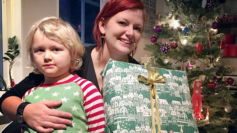 Sabine Dahlberg från Hara sitter med sonen och håller i julklapp