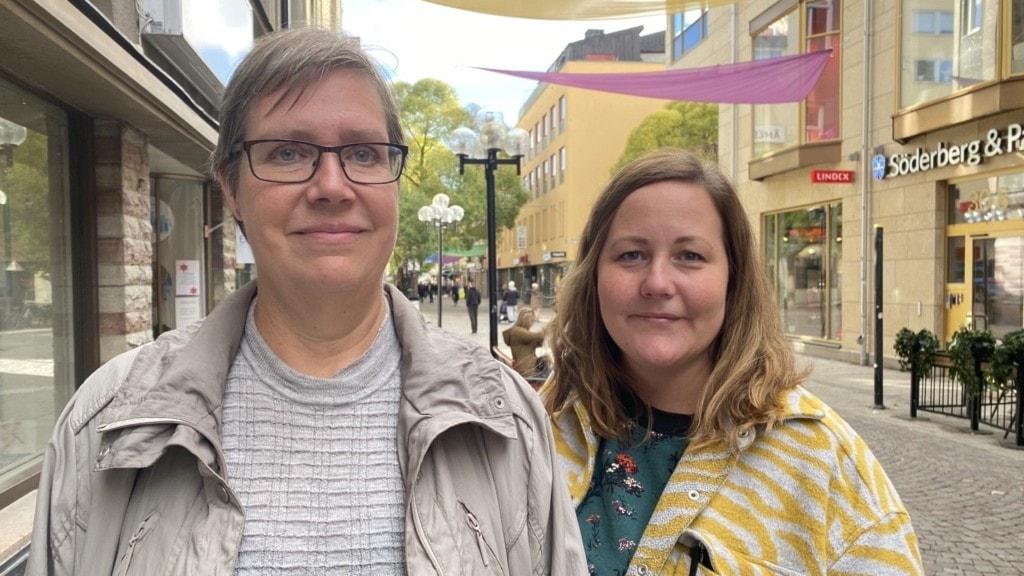 Två kvinnor står utomhus längst en gågata i stadscentrum.