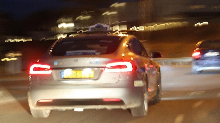 Kvällsbild med oskärpa av taxibil i stadsrondell