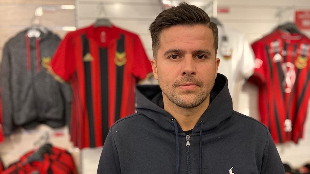 En man i svart tröja står framför några fotbollströjor.