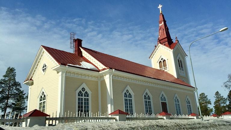 Kyrkobyggnad med ljusgula träväggar och rött plåttak