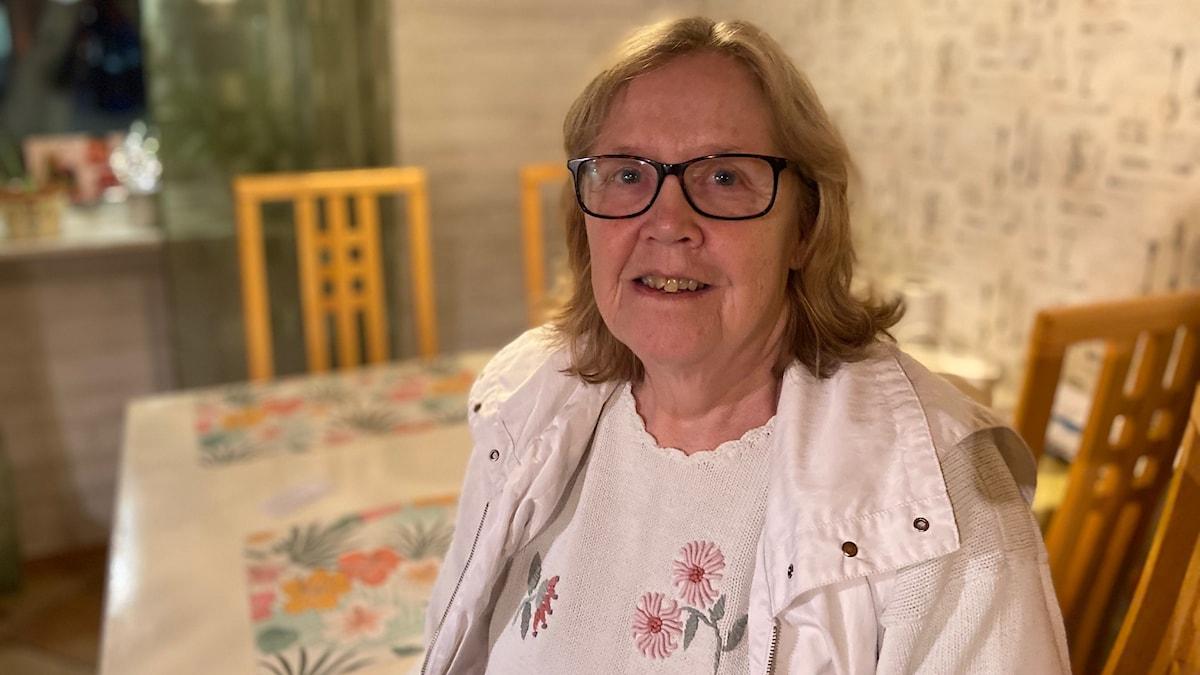 Äldre kvinna klädd i svarta glasögon och ljusa kläder står eller sitter framför ett köksbord och ler mot kameran.