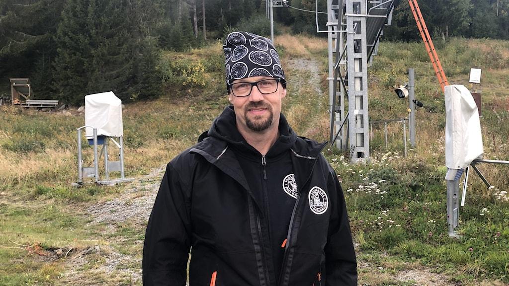 Man i mörk svart jacka och svartvitmänstrad mössa står vid liftanläggning med barmark