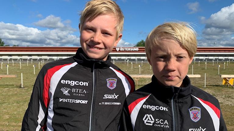 Två ljushåriga pojkar om tittar in i kameran