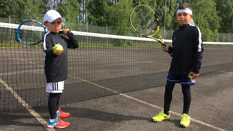 Två pojkar i tenniskläder med racket och boll på en tennisplan