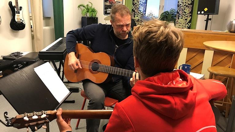 Gitarrläraren Anders Lagroix Kronlund med eleven Jon på Ås skola.