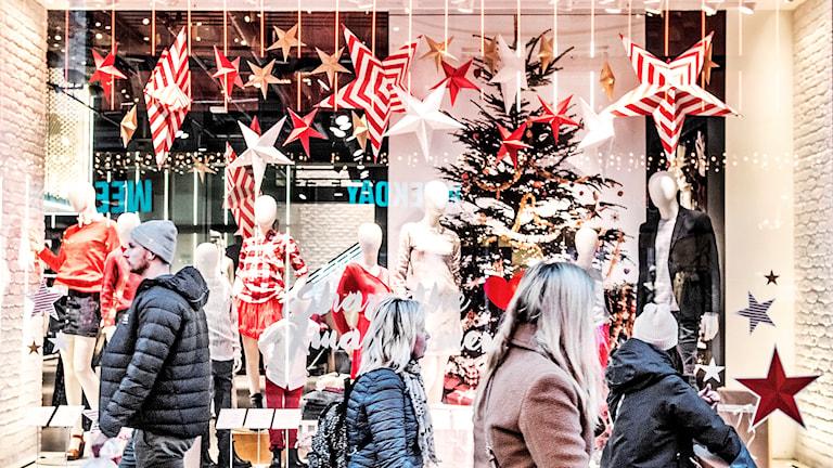 Människor går förbi ett skyltfönster med julstjärnor och annat julpynt