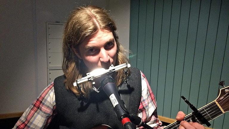 ung man spelar munspel och gitarr