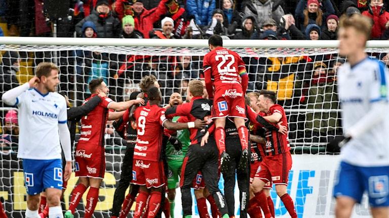 Flera fotbollsspelare kramar om varandra efter seger