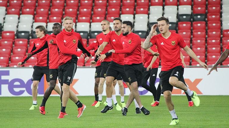 Fotbollsspelare klädda i rött och svart tränar på fotbollsarena.