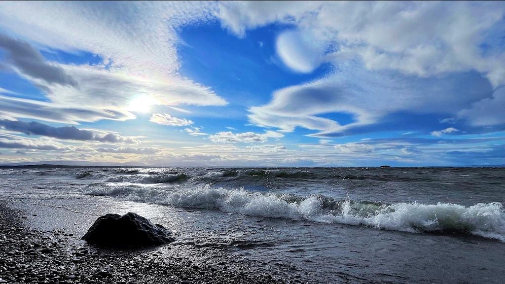 Kraftiga vågor på insjö och ovan en blå himmel med vita moln som formar ett hjärta