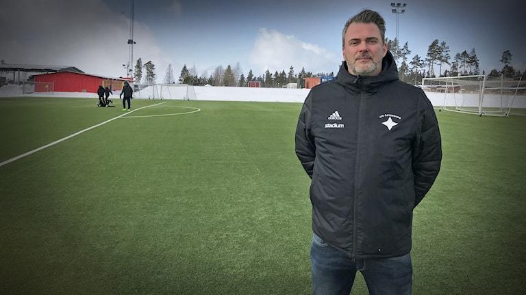 En man i svart jacka står på en fotbollsplan med några spelade killar i bakgrunden.