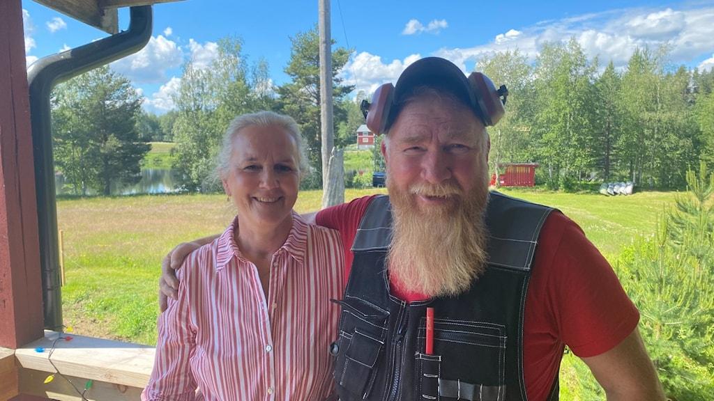 en kvinna i rödvit skjorta och en man med långt ljust skägg, en keps och gräsklipparhörlurar över öronen står på en veranda i Härjedalen