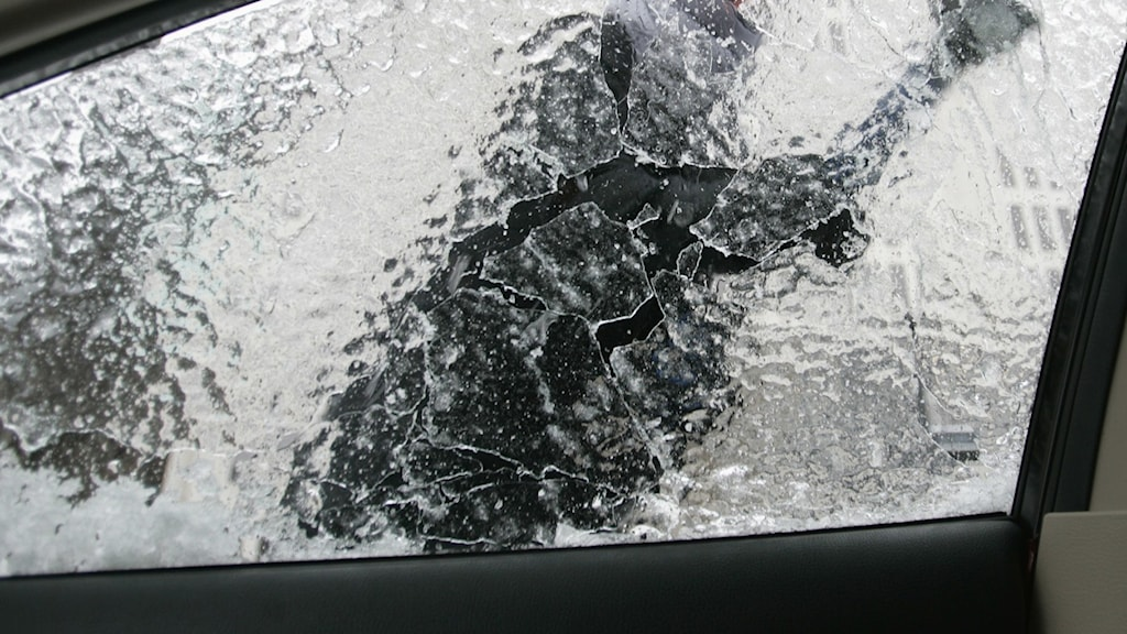 En man står och skrapar bort isen från sidorutan på en bil.