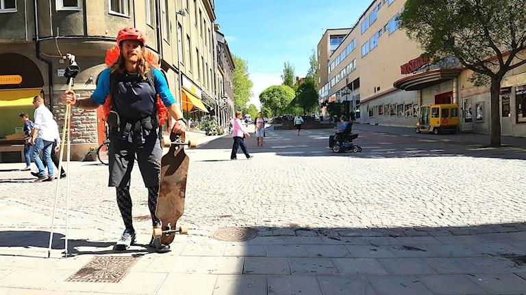 Man står med ryggsäck på gata och håller i longboard