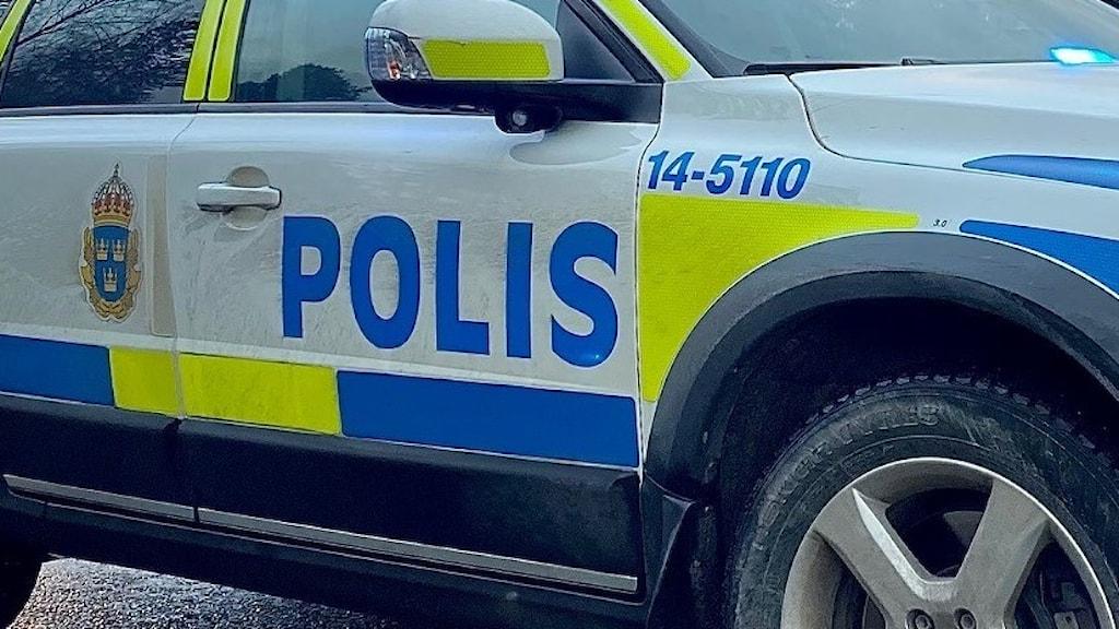 En polisbil som står på vägen med blåljusen på.