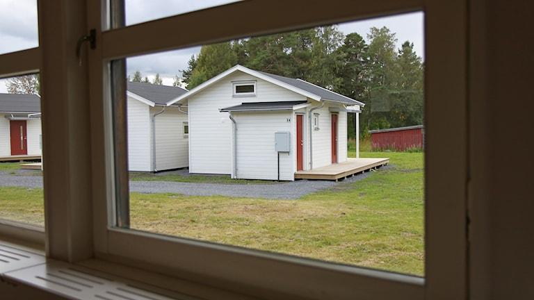 Vy genom fönster mot vita småhus