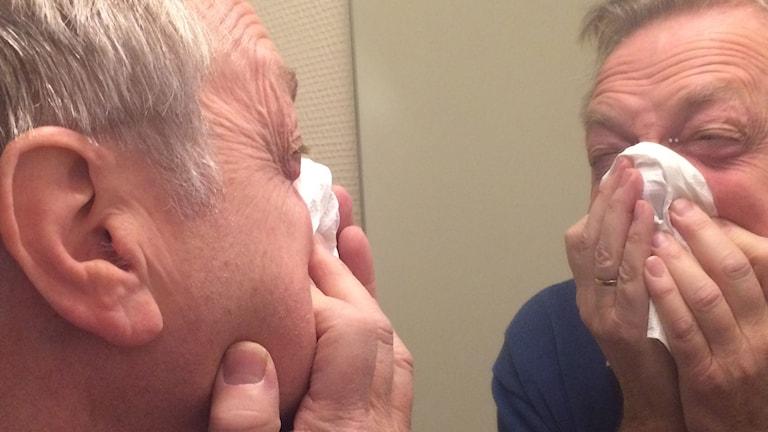 En man snyter sig framför spegel
