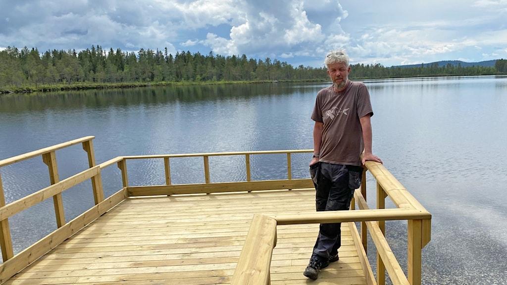 Man står på träbrygga vid sjö