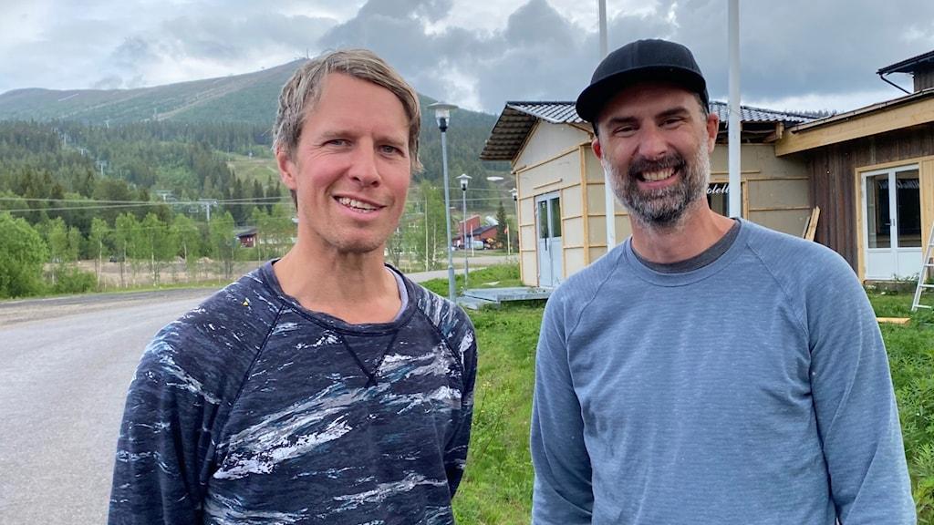 Två män står framför hotellbyggnad i fjällmiljö