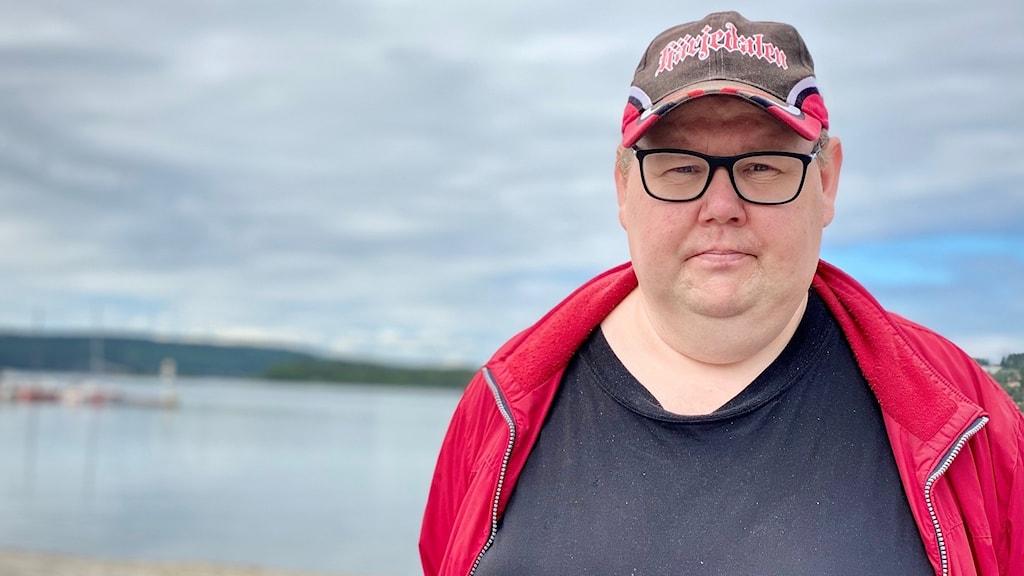 En man med keps och fyrkantiga glasögon.