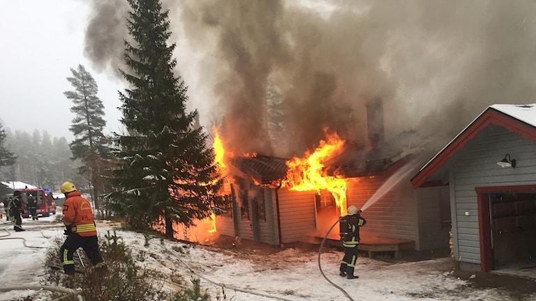 Brandmän försöker släcka fritidshus står i lågor