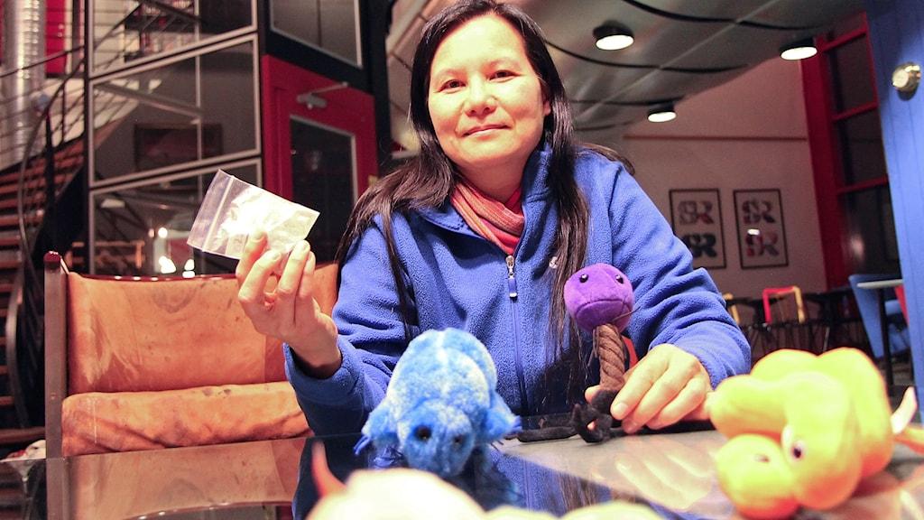 Mörkhårig kvinna med gosedjur framför sig på ett bord