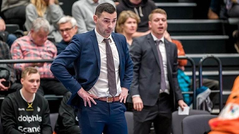 En man i blå kostym ser med sträng blick på en basketplan, en läktare i bakgrunden.