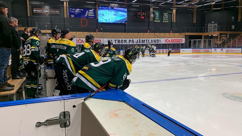 ishockeyspelare i ishockeymundering står lutad i båset och tittar på en match