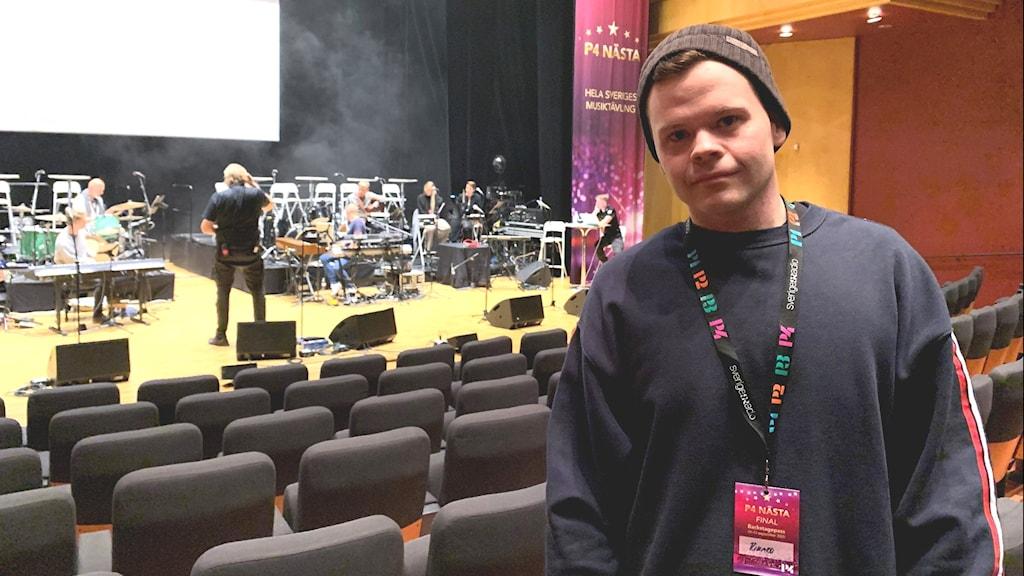 En kille i toppluva och collegetröja i en konsertlokal