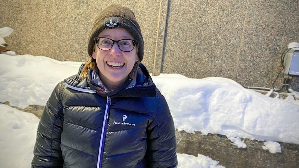 En kvinna med täckjacka, mössa och glasögon står utanför framför en snöig tegelvägg.
