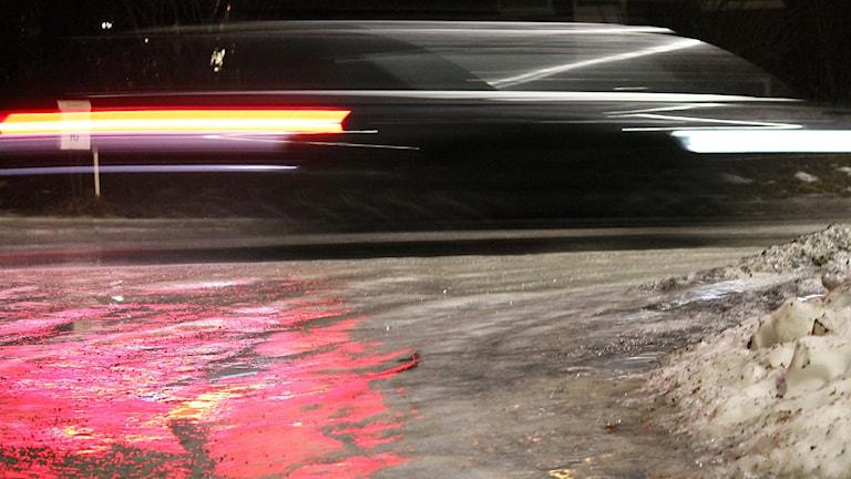 Bil passerar på gata med ishalka