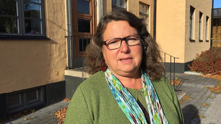 Kvinna står i grön kofta framför offentlig byggnad.
