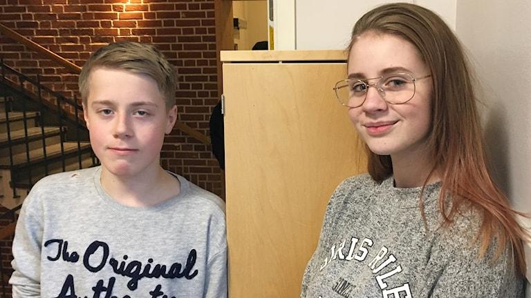 Två elever i tonåren, en kille och en tjej, står i korridor på skola