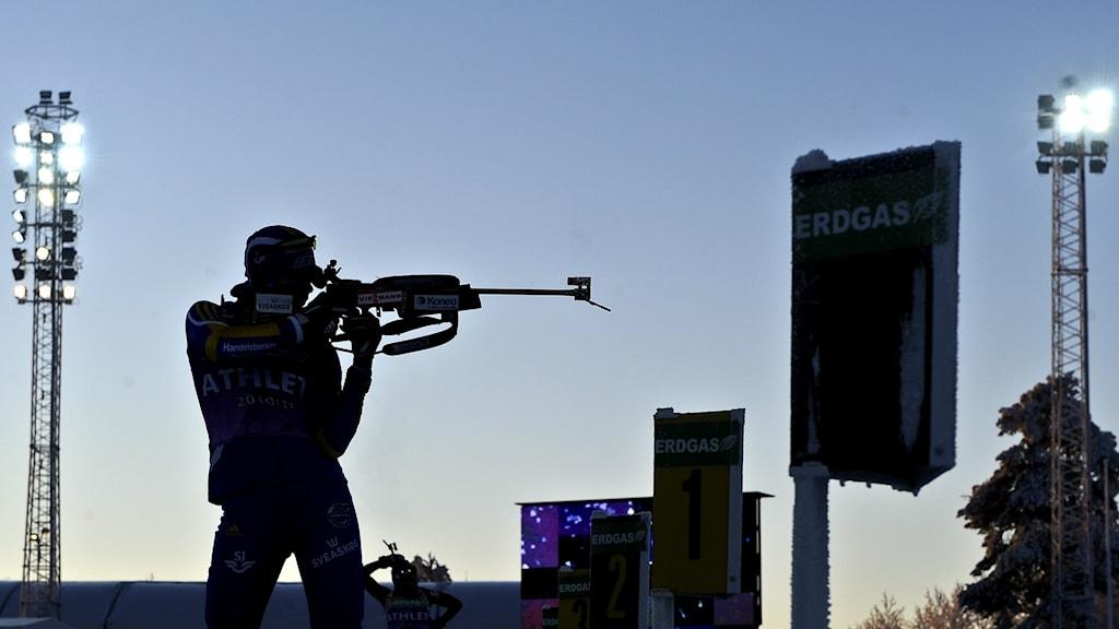 silhuett av skidskytt som skjuter, stående, på skjutvallen