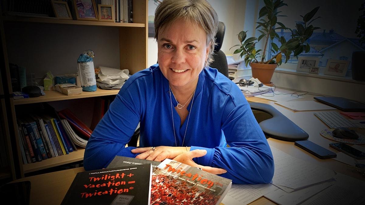 Kvinna i kontor bakom en bunt böcker vid ett skrivbord.