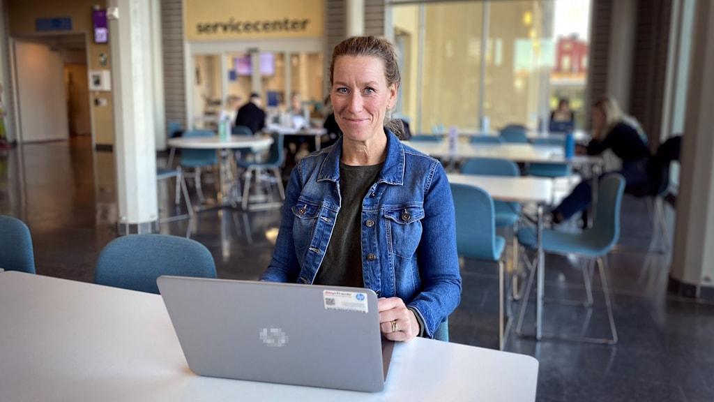 Kvinna bakom bärbar dator, framför flera människori bakgrunden som arbetar tillsammans samlade vid bord.