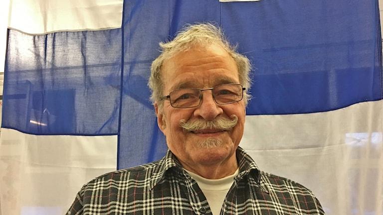 Man med mustasch och glasögon framför finska flaggan