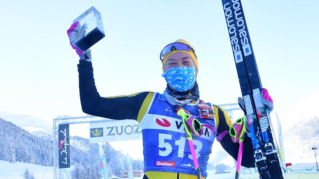 Glad kvinna med längdskidor i vänstra handen och en pokal i glas i den högra.
