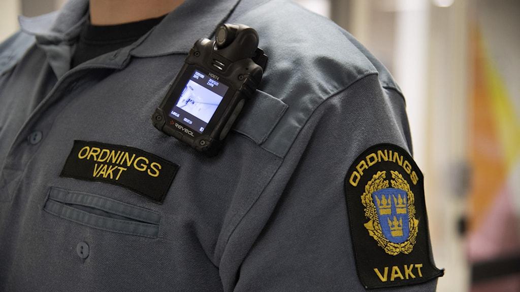 Närbild på en person som har blå kläder på sig där det står ordningsvakt.