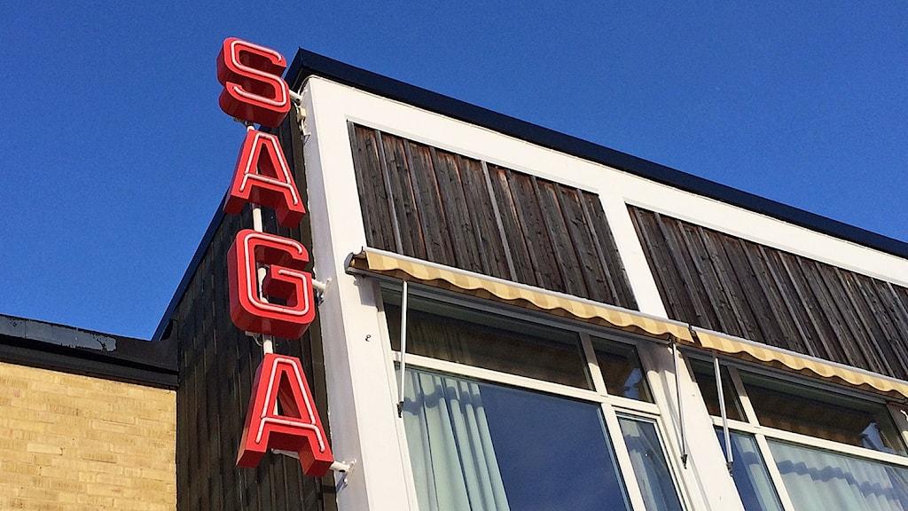 """Tegelbyggnad med ljusskylt """"Saga"""""""