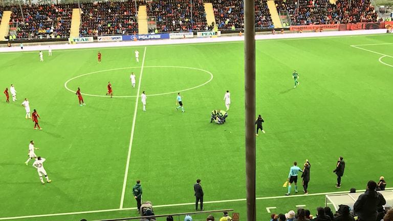 Vakter brottar ned åskådare på fotbollsplan