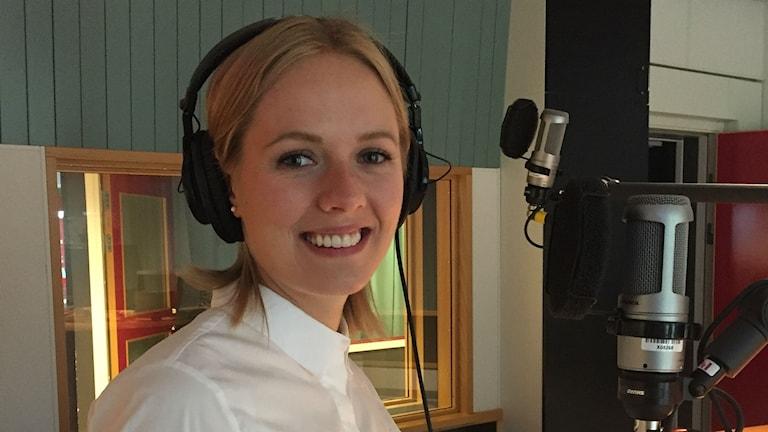 Ljus, ung kvinna, iklädd vit skjorta, står i en radiostudio.