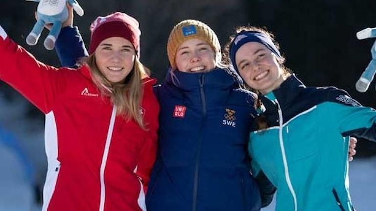 Tre tjejer med röd, blå och turkos jacka och skidkläder.