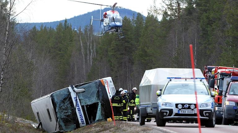 Räddningsinsats med flera fordon och polishelikopter vid bussolycka
