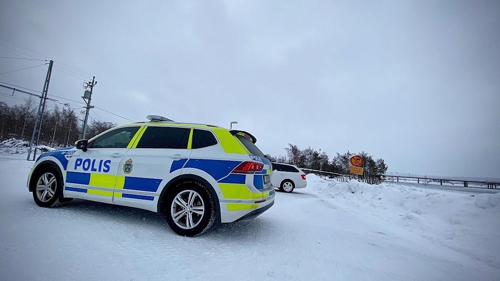 En polisbil som är gul, blå och vit står på en snöig parkering.